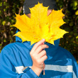 The teenager with a yellow sheet of a maple. Solar autumn. — Stock Photo #3913079