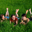 Stock Photo: Girls lay in green summer grass