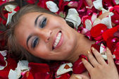 Smiling girl in rose petal — Stock Photo