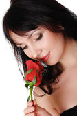 Young lovely brunette with a beautiful red rose — Stock Photo