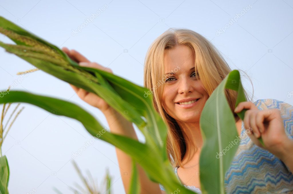 Young girl on a background of green maize and blue sky — Stock Photo #3632668