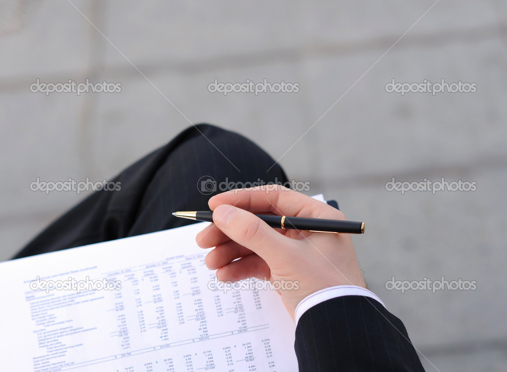Young business man writes a handle on sheets of paper sitting on the street — Stock Photo #3873687