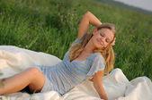 Jeune fille assise sur l'herbe verte — Photo
