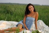 Niña sentada sobre la hierba verde — Foto de Stock