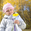 Little girl with a yellow flower — Stock Photo