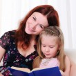 Little girl and her mother read a book — Стоковая фотография