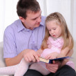 Ittle girl is sitting on the lap of his father — Stock Photo