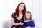 Holčička a její matka číst knihu — Stock fotografie