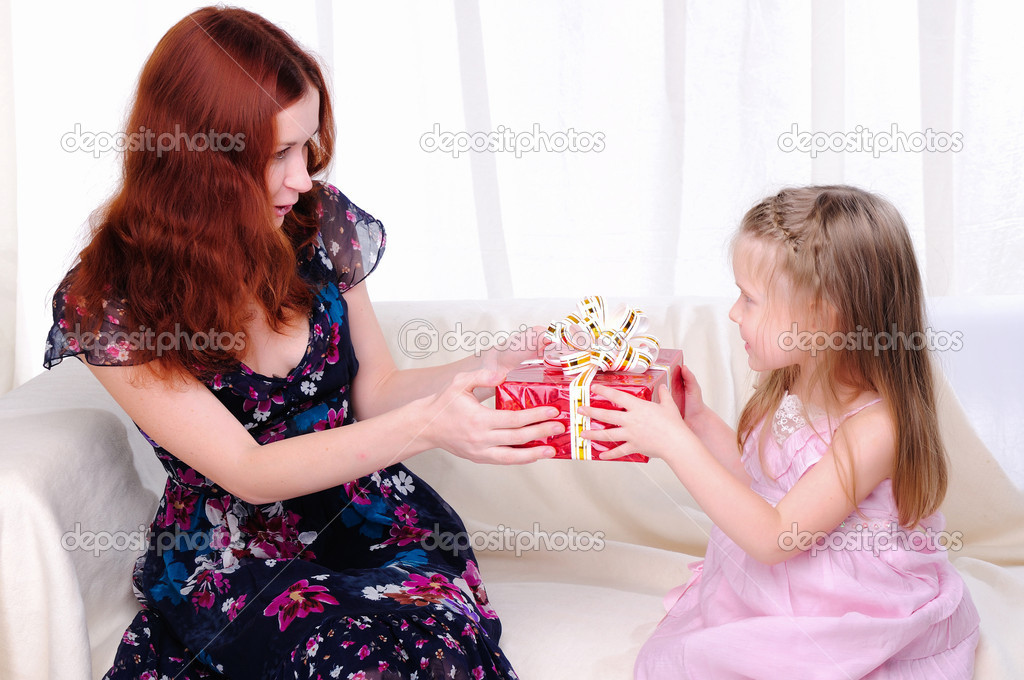 Little girl mom gives a holiday gift in red box with white ribbon.  Stock Photo #4123305