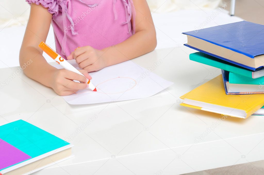 A little girl draws on the album with a pen — Stock Photo #4130515