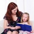 Little girl and her mother read a book — Stock Photo #4141949