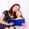 Little girl and her mother read a book - Photo