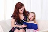 Маленькая девочка и ее мать читать книгу — Стоковое фото