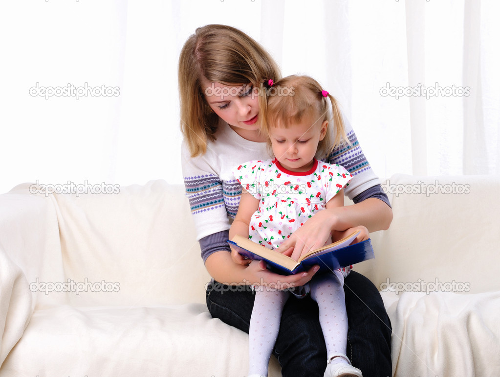 Mother and daughter reading a book together on the couch  Stock Photo #4162243