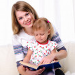 Mother and daughter reading a book — Stock Photo