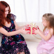 Little girl mom gives a holiday gift — Stock Photo