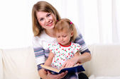 Mother and daughter reading a book — Stockfoto
