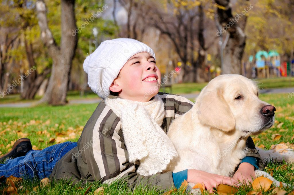 Boy playing in autumn park with a golden retriever. — Stock Photo #4174029