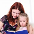 Stock Photo: Little girl and her mother read a book