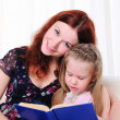 Little girl and her mother read a book - Stock Photo