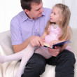 Ittle girl is sitting on the lap of his father — Stock Photo #4187119