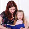 Little girl and her mother read a book — Stock Photo #4230156