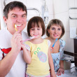 Mom, daughter and father brush their teeth — Stock Photo #4245429