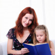 Little girl and her mother read a book — Stock Photo