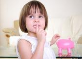 Little girl hides her money — Stock Photo
