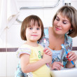 Mother and daughter brushing their teeth - Stock Photo