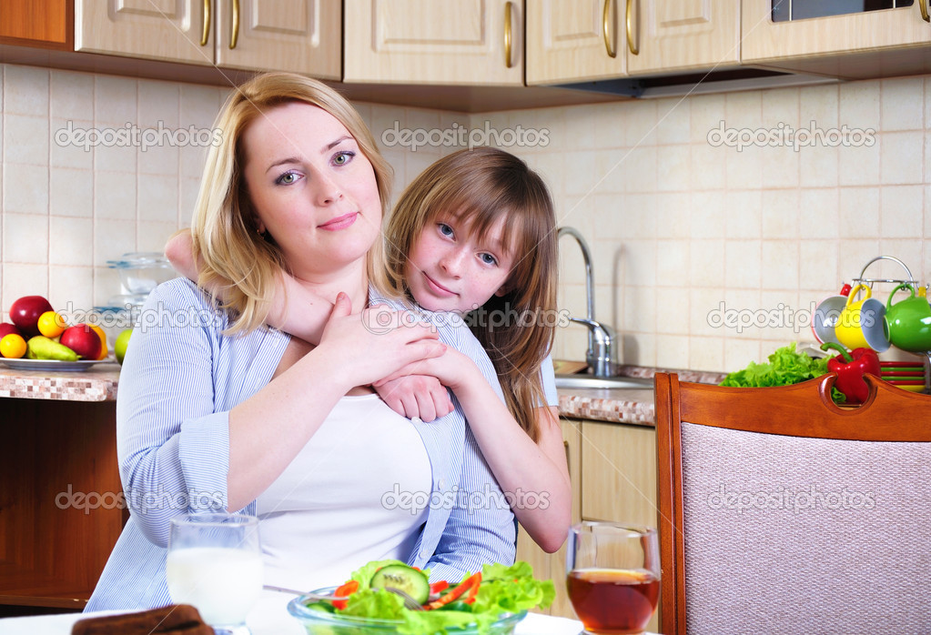 Mom and young daughter eating breakfast together in the kitchen  Stock Photo #4277646