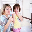 Mother and daughter brushing their teeth — Stock Photo
