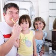Stock Photo: Mom, daughter and father brush their teeth