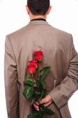Young man hides behind a rose — Stock Photo