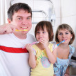 Mom, daughter and father brush their teeth — Stock Photo