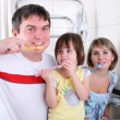 Mom, daughter and father brush their teeth — Stock Photo #4468124