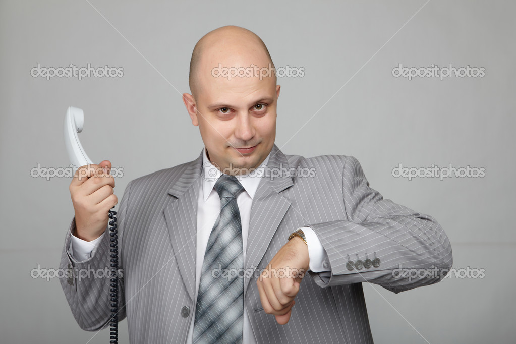 Bald businessman with the handset in hand and wearing a gray suit. — Stock Photo #4470153