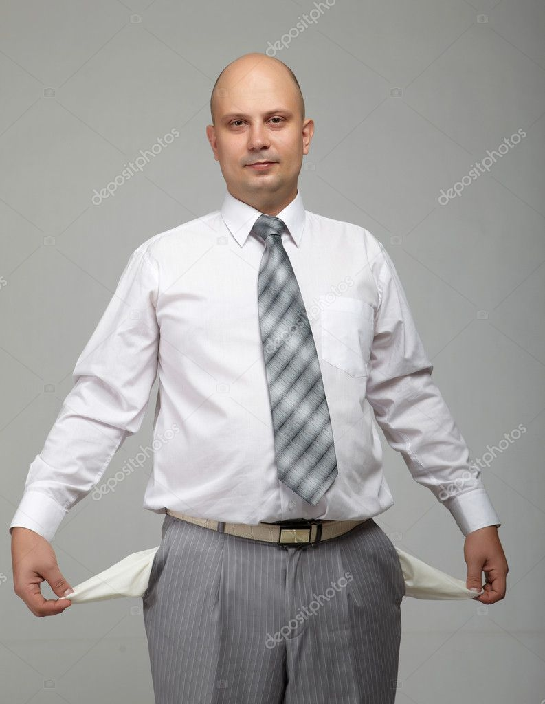 Bald businessman in a gray suit with a gray background with recurving pockets — Stock Photo #4487920