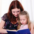 Little girl and her mother read a book - Стоковая фотография