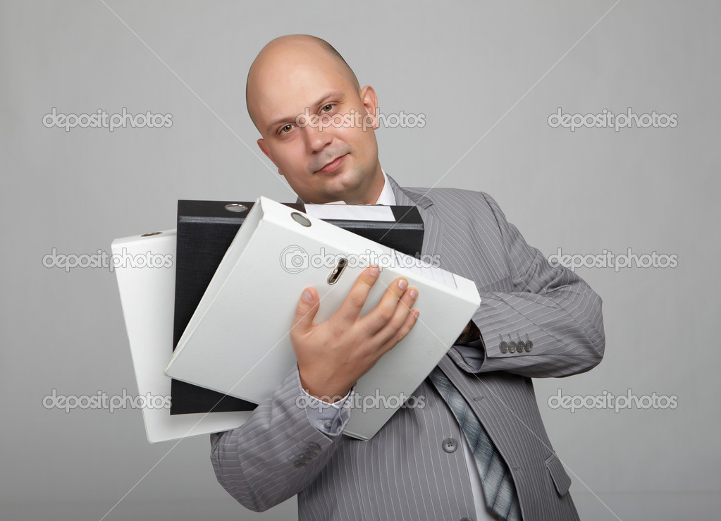 Bald businessman in a gray suit with a gray background with folders for papers in their hands — Stock Photo #4505157