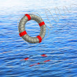 Lifebuoy white against the blue sea - Stock Photo