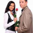 Young man gives his girlfriend a rose - Zdjęcie stockowe