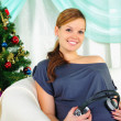 Pregnant woman holding headphones - Stock Photo