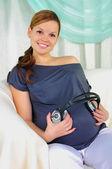 Pregnant woman holding headphones — Stock Photo
