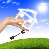 Casa en las manos contra el cielo azul — Foto de Stock