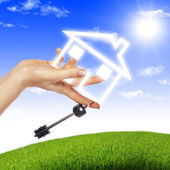Dom w rękach przeciw błękitne niebo — Zdjęcie stockowe