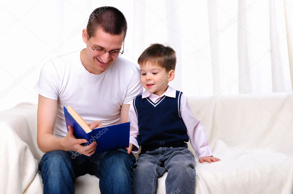 Father and son reading a book together on the couch — Stock Photo #4515482