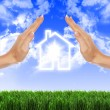 House in the hands against the blue sky - Stock Photo