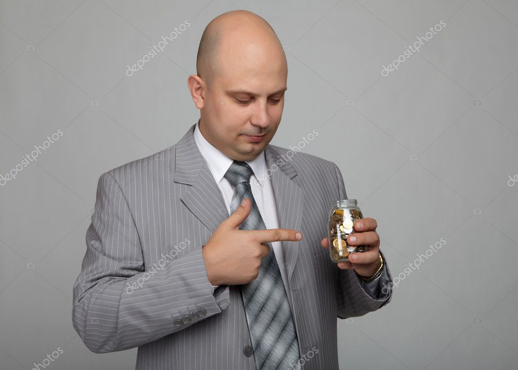 Bald businessman in a gray suit with a gray background with a can with coins in hand  Stock Photo #4521015
