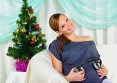 Gravid kvinna anläggning hörlurar — Stockfoto